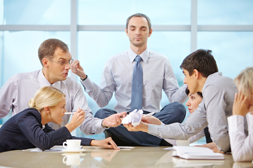 Furious arguing business team and CEO meditating in lotus position on the table