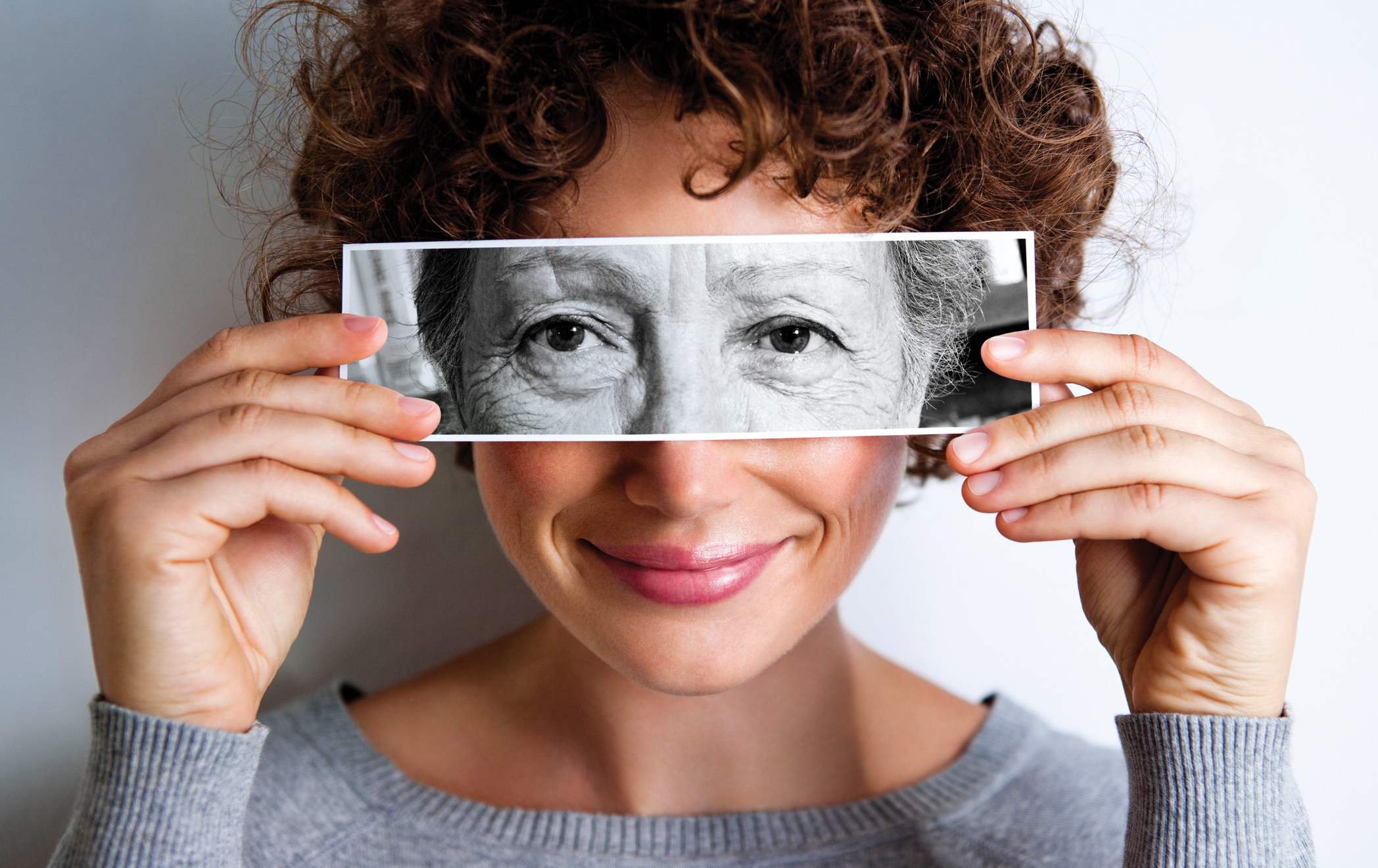 Woman with photo of elderly woman's eyes on hers'